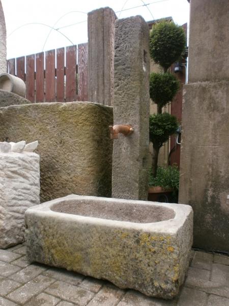 historischer Brunnen mit Sandsteintrog und antiker Stele