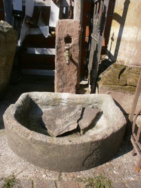 Halbrunder Sandsteinbrunnen mit antikem Speier